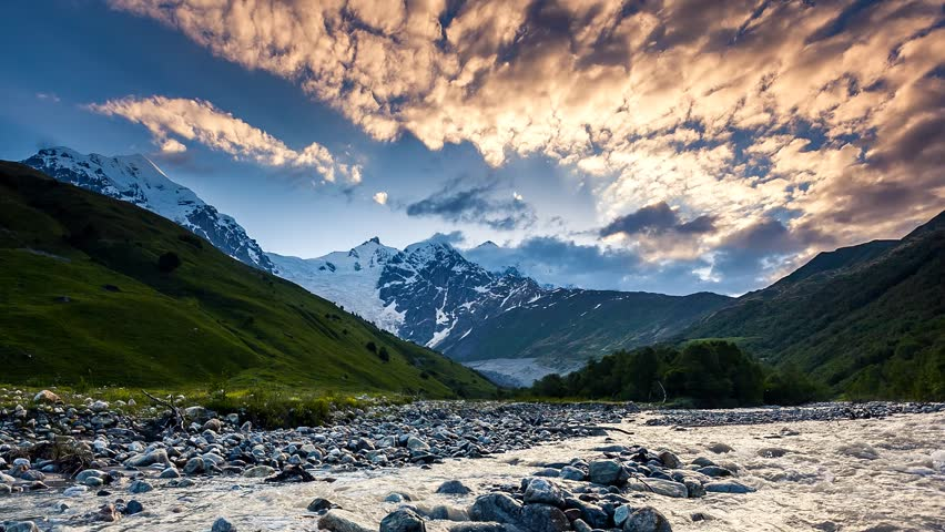 Time lapse clip. River in mountain valley at the foot of Tetnuldi glacier. Upper Svaneti, Georgia, Europe. Caucasus mountains. Beauty world. HD video (High Definition).