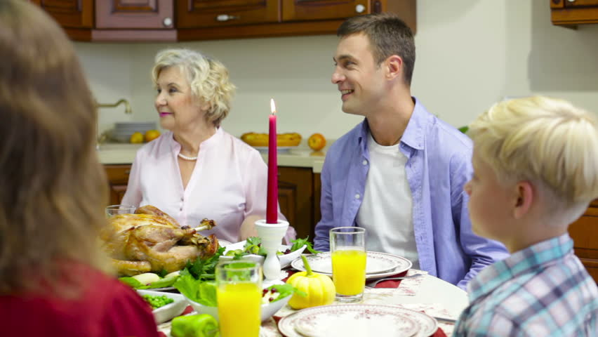 Family gathered at festive dinner saying a prayer before eating