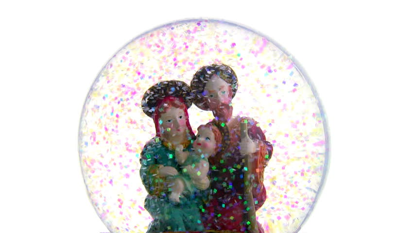Joseph and Mary with baby Jesus in her arms. Glass ball with toy figures on a white background. The blizzard of multicolored sequins