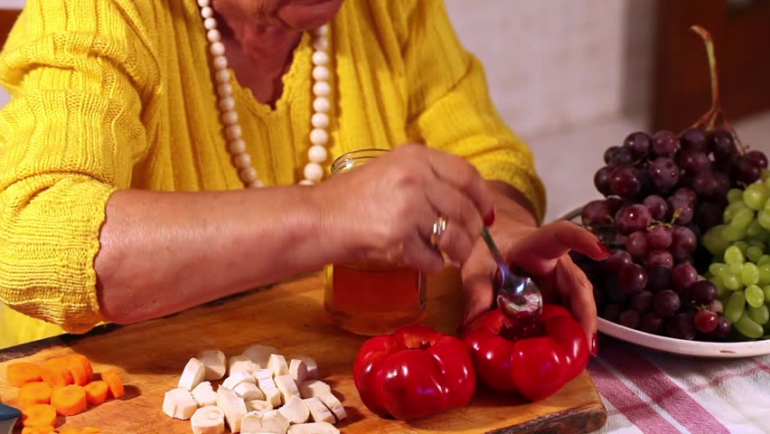 Senior woman preparing pickled tomato peppers filled with grapes.