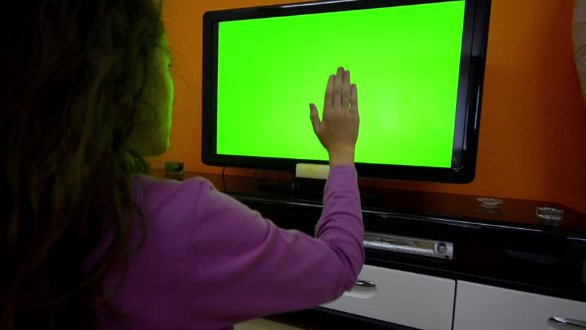 Girl with smart TV touchless touchscreen gestures dolly shoot zoom, 1080. Beautiful teen girl makes touchless control on smart tv without touching it on green screen chrome key greenscreen dolly shot