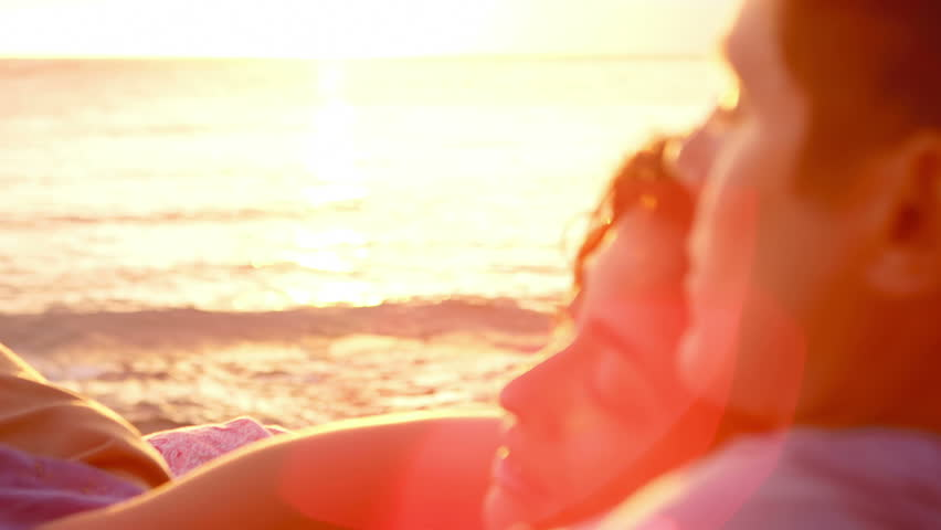 A woman lays on a man's chest as they sit on the beach and watch the sun set together | Shutterstock HD Video #4776395