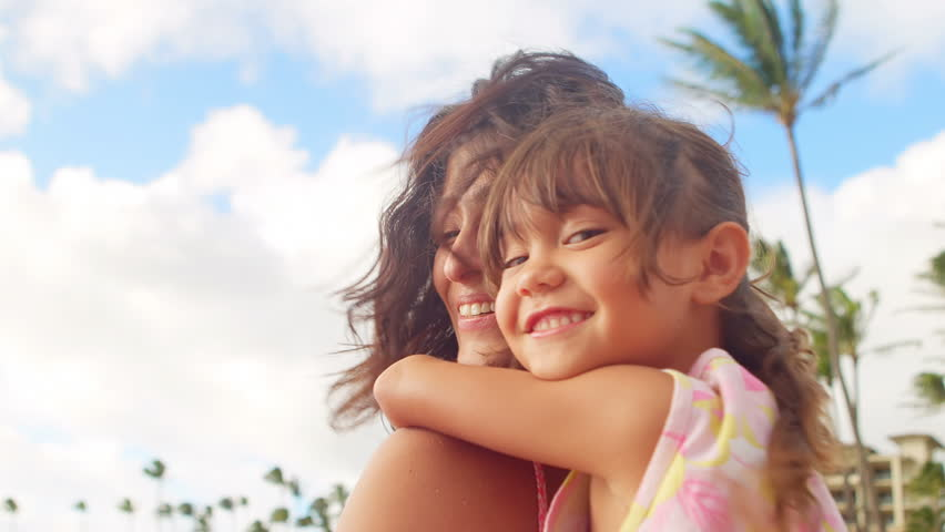 A mother holds her daughter on her back and smile into the camera