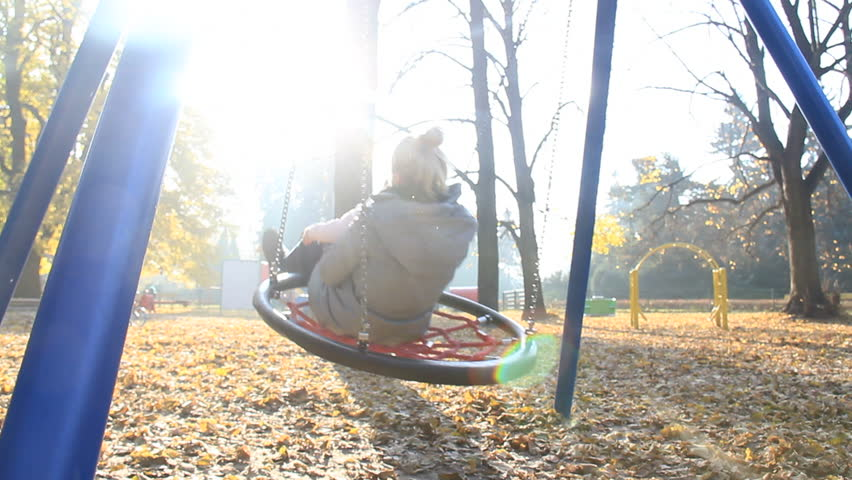 Mother and child play on swing at the playground in autumn with flare