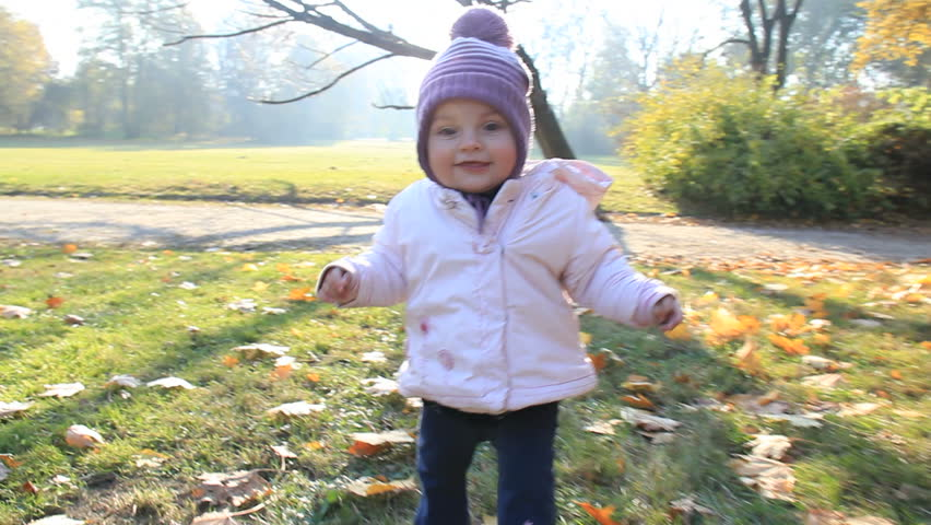 Cute baby learns to walk in a park