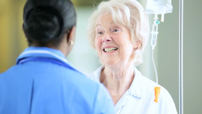 Elderly patient receiving intravenous fluid chatting with devoted African American nurse in hospital corridor | Shutterstock HD Video #4807469