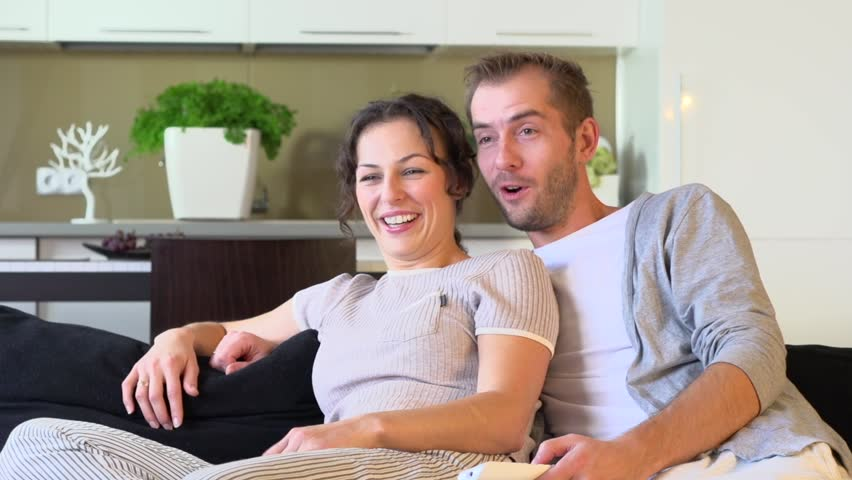 Young Couple Watching TV on the Sofa in the Living Room. Hugging and Laughing Family Watching Comedy Movie at Home Together. Dolly Shot