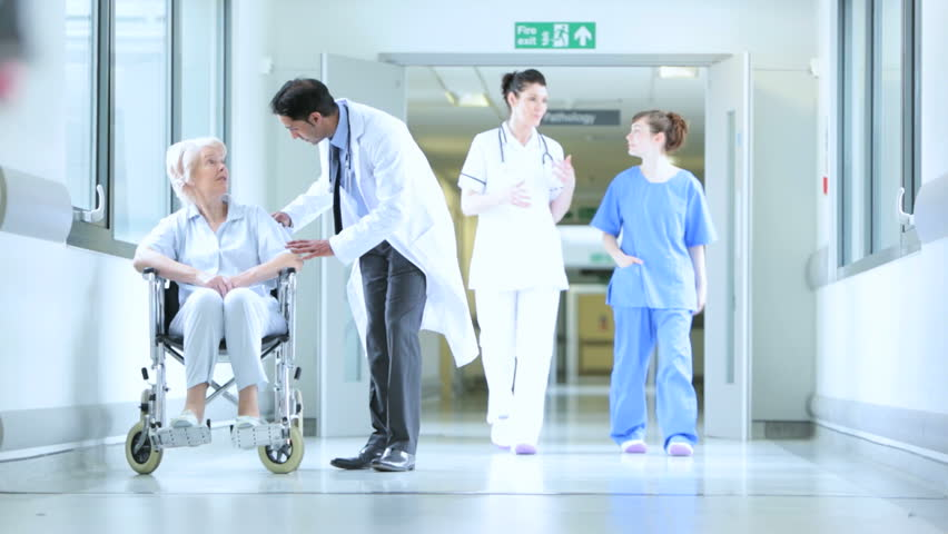 Multi-ethnic medical staff talking about patient care in busy hospital hallway and moving patient in wheelchair