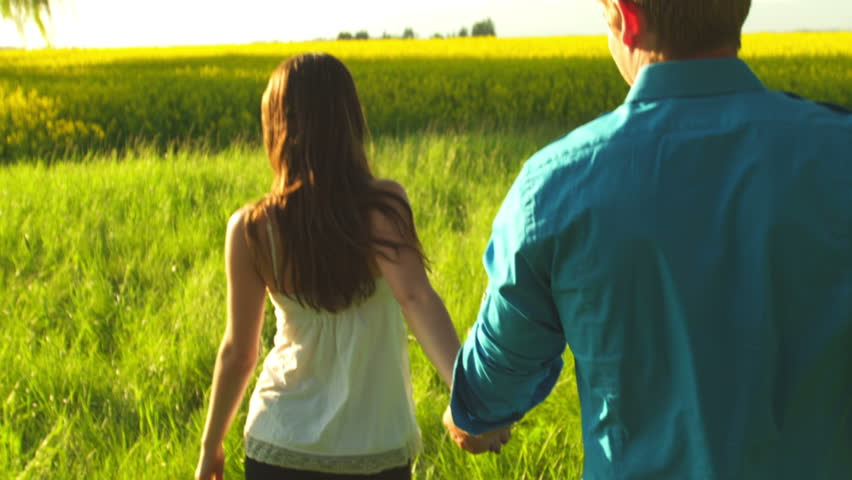 A young couple holds hands as they walk through an open field as the camera follows them   Shutterstock HD Video #4840529