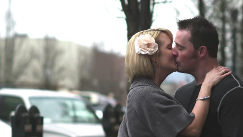A couple kiss romantically on the street. Aww