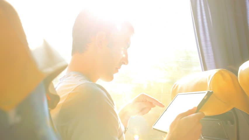 A young man looks through his tablet as he takes a bus ride #4852694