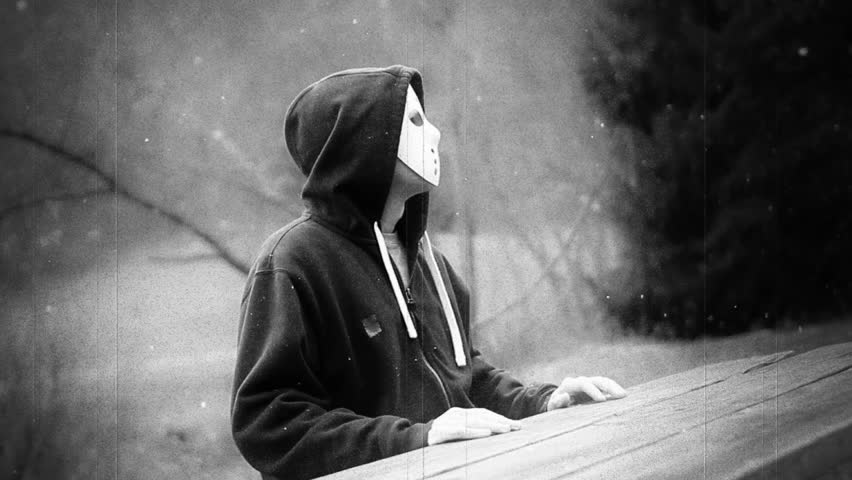 A retro stylized film look of a masked killer sitting in the forest.