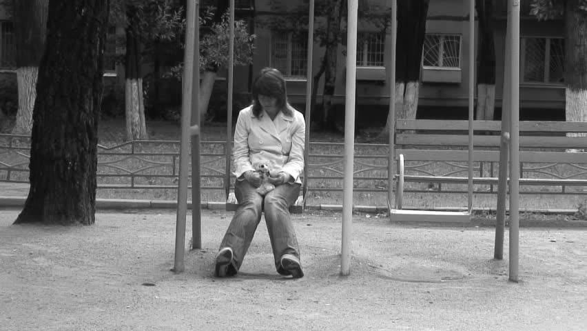Alone woman in deep depression on a swing with Teddy bear. Black and white.