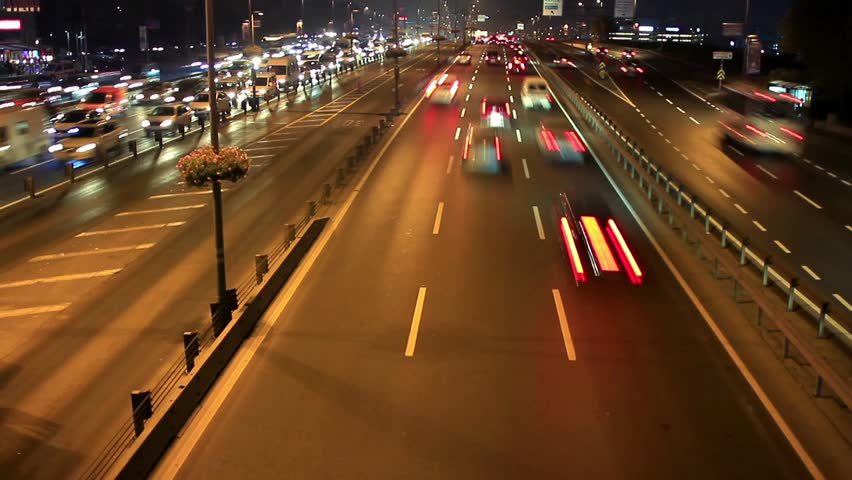 Highway through city at night time lapse. Busy light trail traffic on a freeway of Istanbul.