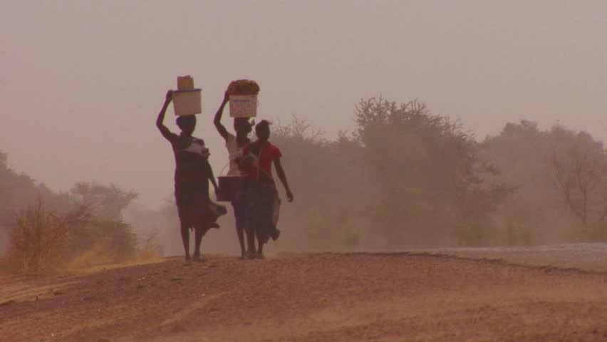 MALI-CIRCA 2012-Women walk carrying goods on their heads through the Sahara desert in mali.