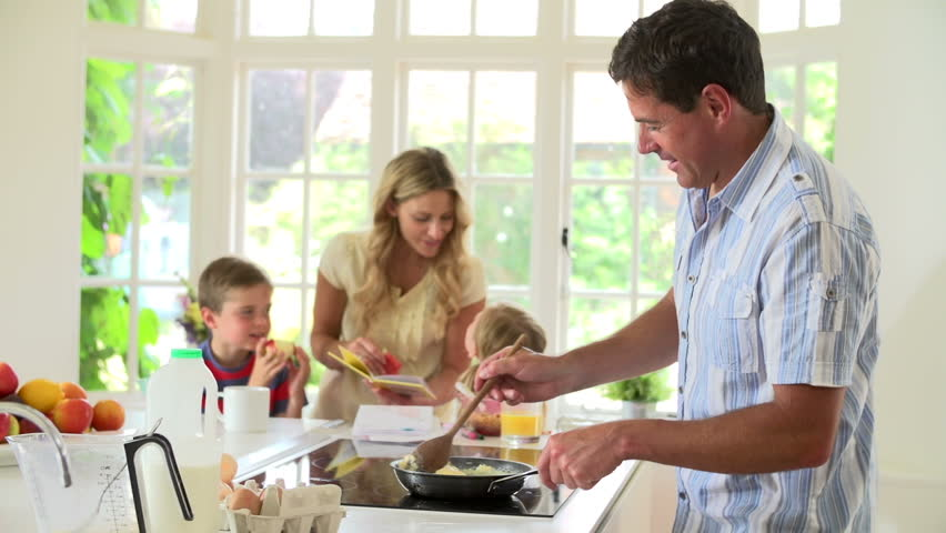 Father makes breakfast for family as mother reads to young children in kitchen #4877333