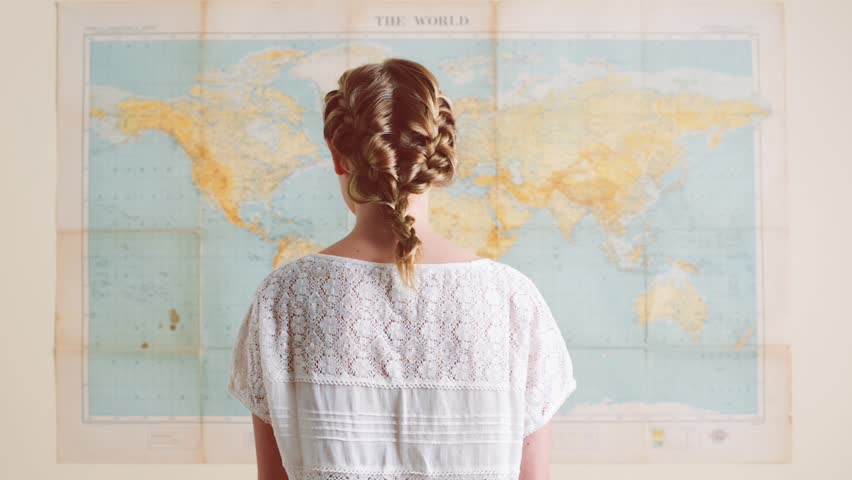 femme qui regarde une carte du monde
