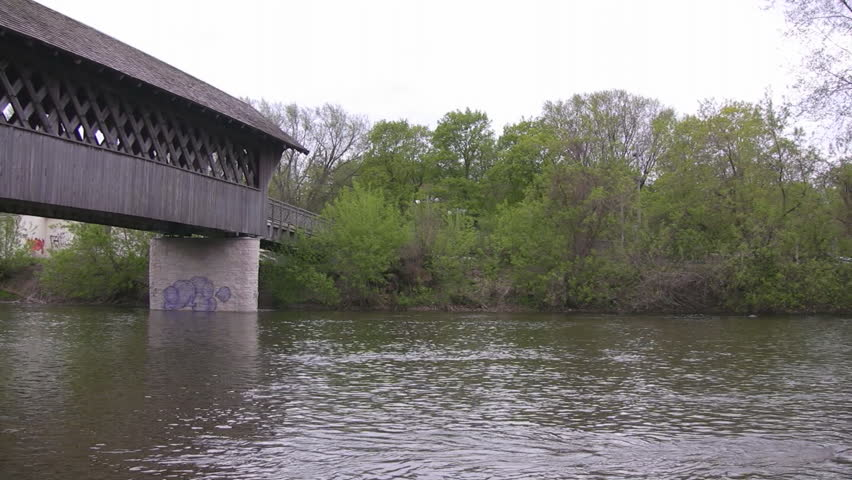 A pan along the length of a wooden covered walking bridge, shot from the river below.  Guelph, Ontario, Canada