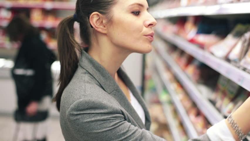 Woman in supermarket choosing ham from the fridge  | Shutterstock HD Video #4912484
