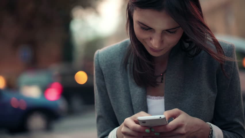Elegant beautiful woman texting on smartphone in the city  | Shutterstock HD Video #4925081