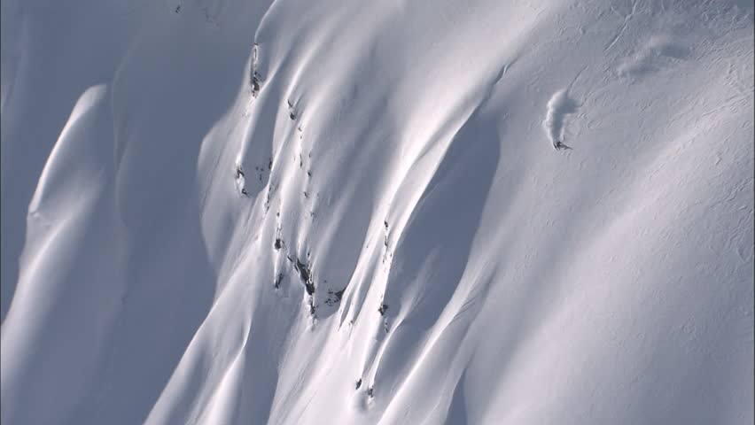 Skier charging down a perfect powder covered face with a bluebird sky.