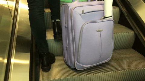 Girl with baggage on the escalator