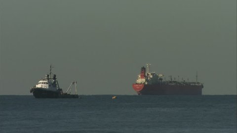 A large fishing boat and a huge transport ship floating in the ocean