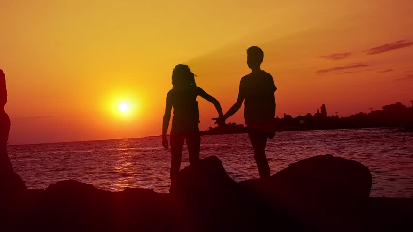 HD: Romantic Walk - Stock Video. HD1080: Boy and girl as a silhouette are taking a walk on a wonderful evening sky at sunset (sunrise) holding hands. Ocean horizon sunrays shy over heads. Tripod. #4942157