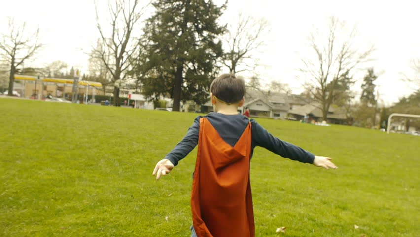 Superhero Boy Runs Around Park Pretending To Fly