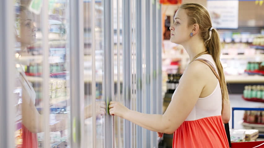 Young woman buying dairy or refrigerated groceries at the supermarket in the refrigerated section opening glass door of the fridge | Shutterstock HD Video #4951547