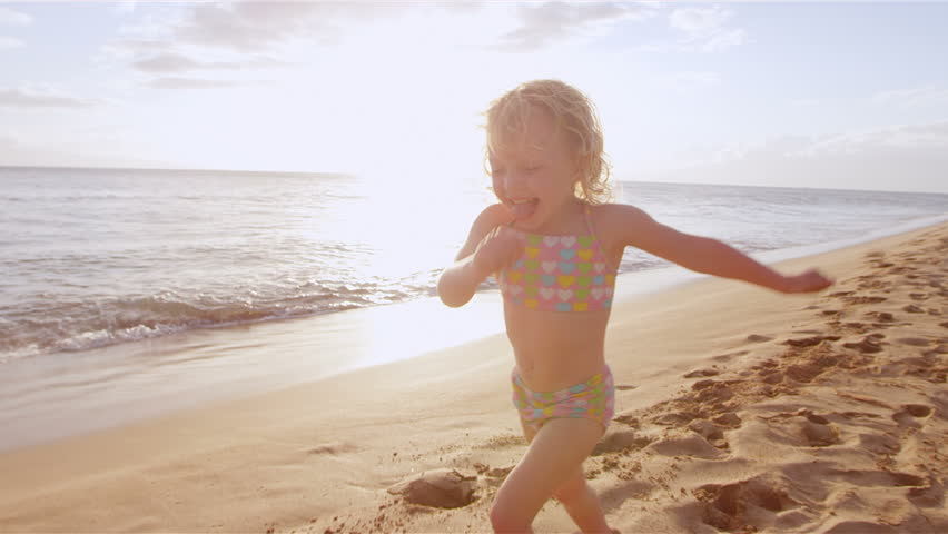 An adorable little girl runs down the beach toward her mother for a big hug and kiss. Close up shot.