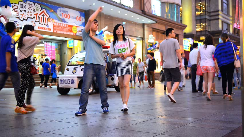 People Cross The Street In The Busy Causeway Bay Shopping