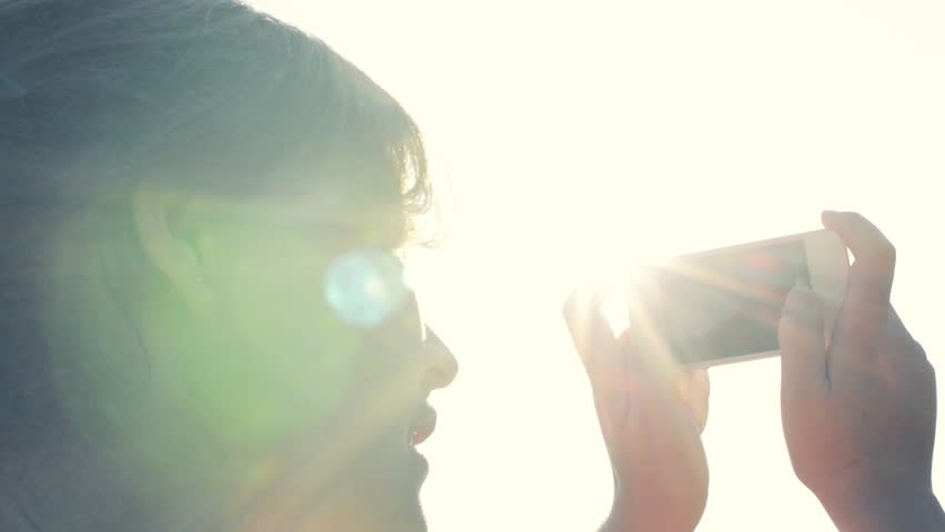 woman taking photographs using mobile phone sunset