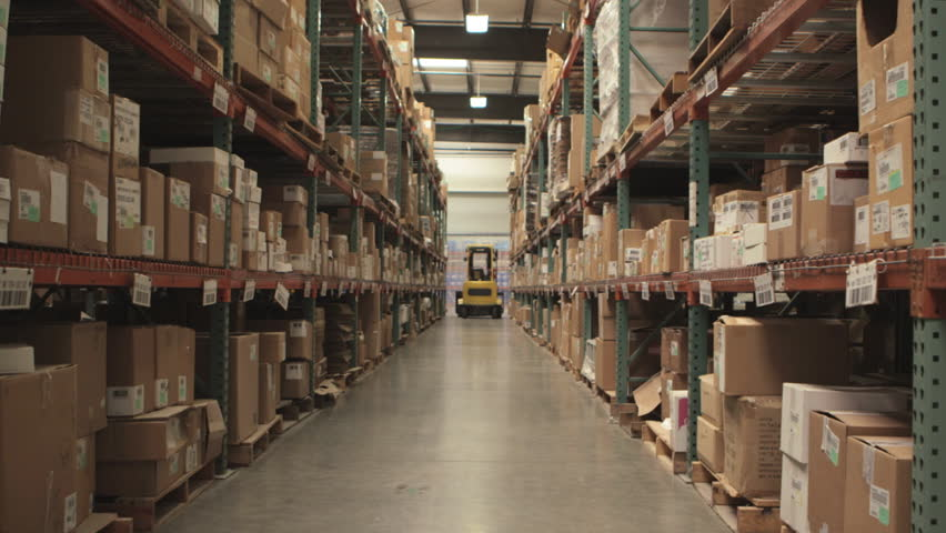 Camera cranes up on shelves of cardboard boxes inside a storage warehouse.  #4993019