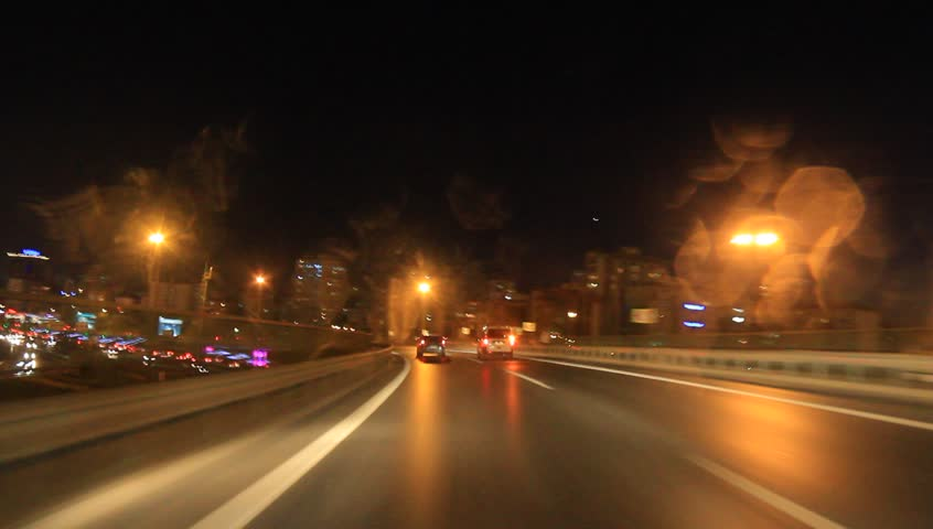 Driving safety during the first rains of the season. Steering on highway exit ramp at night. High definition shot from the car interior.