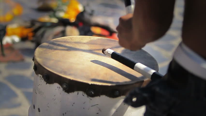 Man playing ceremony drum, video slow motion