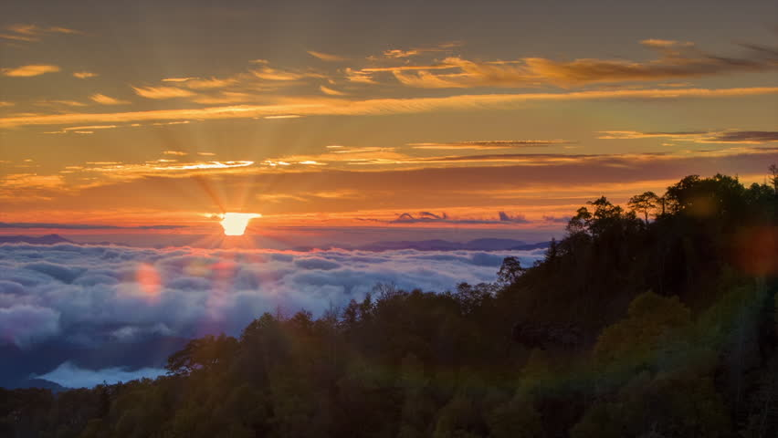 Tilting Up to the Sunrise over the Cloud Covered Smoky Mountains with Sun Rays and Lens Flares following the Camera Movement.
