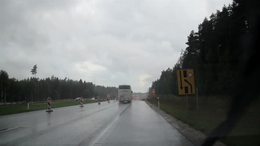 Driving on a rainy day while passing an under-constructed highway. Truck carrying logs at the front slowly passing. A strong rain on the street while on the road.