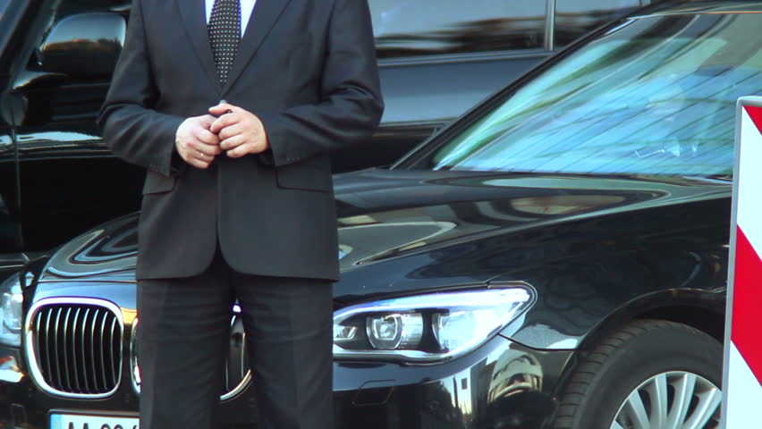 Rich car driver security waits for owner outside business center