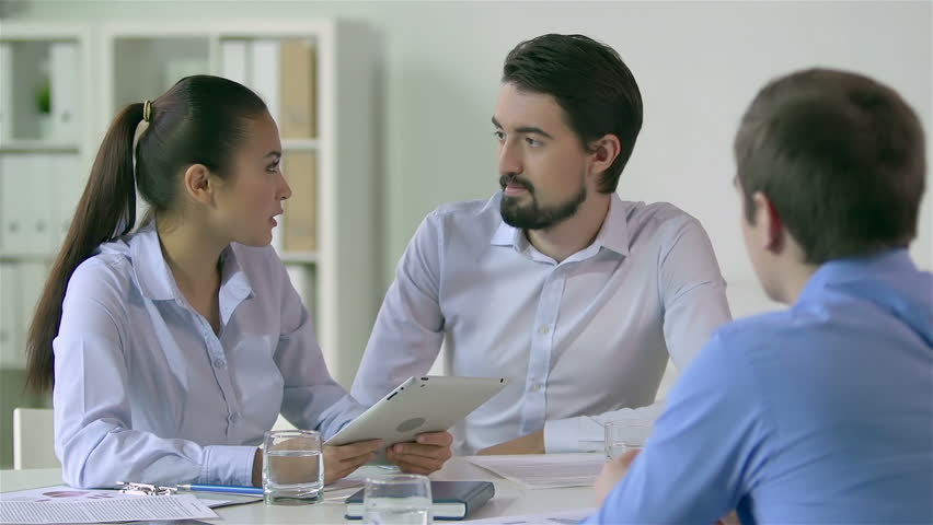 Young executives sitting together to talk over some business matters | Shutterstock HD Video #5089358