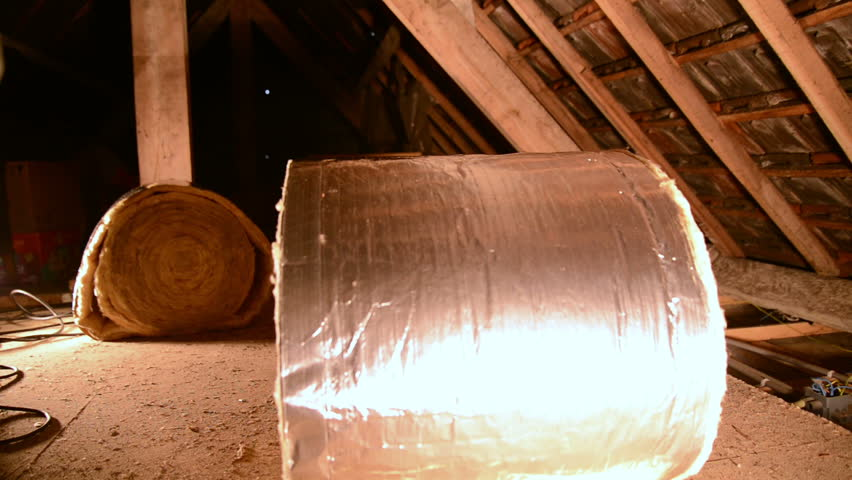 a man rolling out insulation mineral wool.