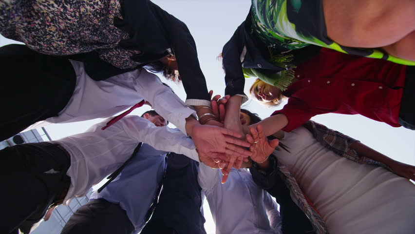 Motivational business team stand in a circle with their hands together for a team talk, outdoors in the city on a bright sunny day. In slow motion. | Shutterstock HD Video #5110193