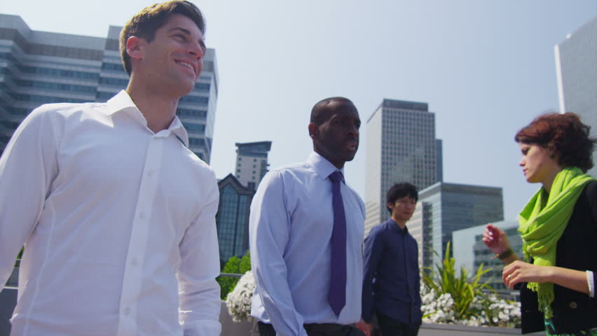 Young mixed ethnicity group of business executives walk and chat together on an outdoor terrace of a city office building with spectacular views of the city skyline. In slow motion.