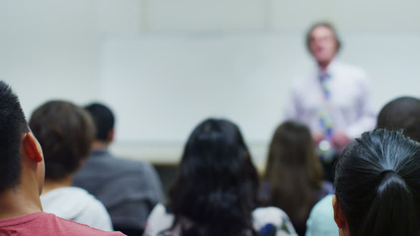 View from behind of a large mixed ethnicity group of students in a classroom, listening as their teacher holds a lecture. One student puts up his hand to ask a question.  | Shutterstock HD Video #5111408