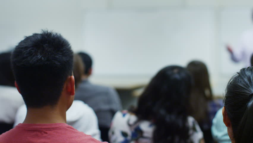 View from behind of a large mixed ethnicity group of students in a classroom, listening as their teacher holds a lecture. One student puts up his hand to ask a question.  | Shutterstock HD Video #5111477