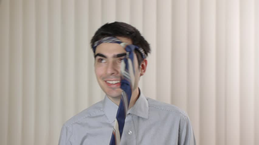 Funny young businessman with a tie around his head
