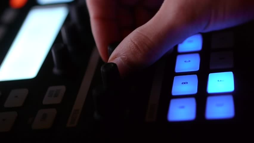 Professional DJ at work during a show with flashing light.