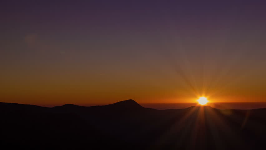 Smoky Mountain Horizion Sunrise with Flickering Rays and Purple Sky as the Sun Rises Above the Blue Ridge Mountains.