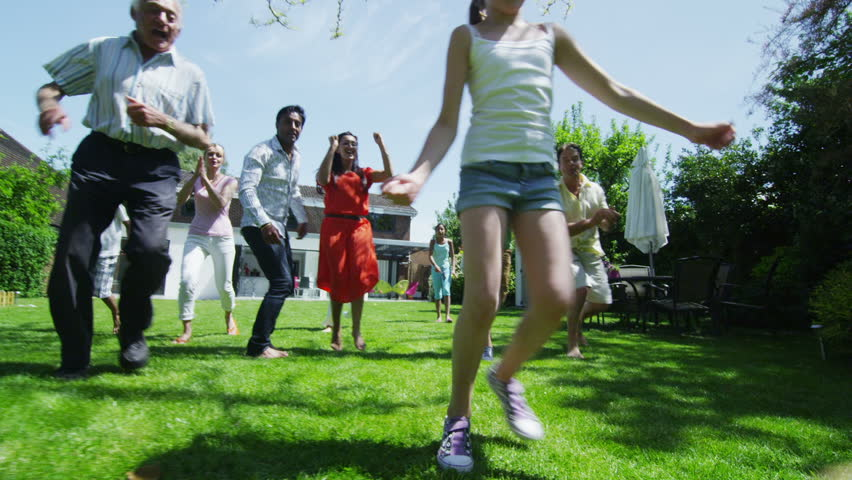 Happy mixed ethnicity group of friends and family with many generations, playing sports and having fun in the garden on a summer day. In slow motion. | Shutterstock Video #5131808