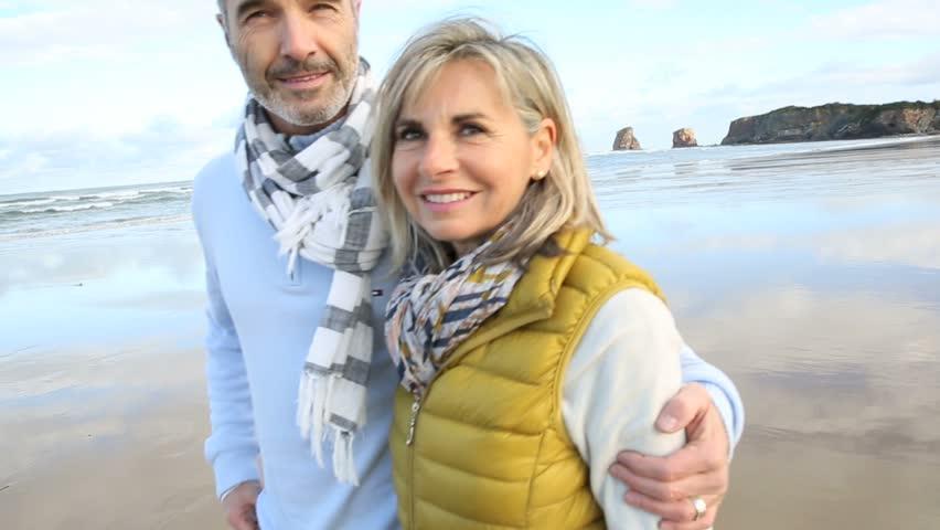 Cheerful senior couple walking on the beach